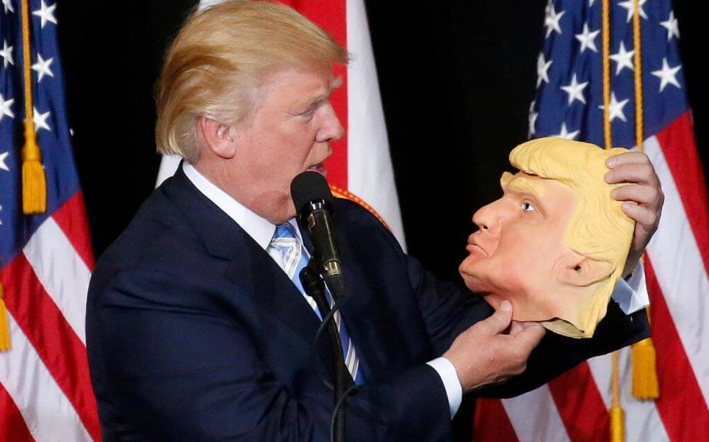113146703_Republican_presidential_nominee_Donald_Trump_looks_at_a_mask_of_himself_as_he_speaks_durin-xlarge_trans_NvBQzQNjv4BqjJeHvIwLm2xPr27m7LF8mUYMapKPjdhyLnv9ax6_too